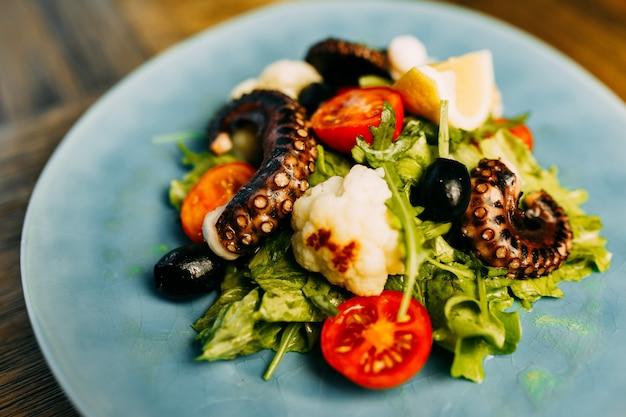 Salade avec poulpe et chou-fleur sur l'assiette.
