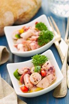Salade de poulpe dans un bol sur bleu