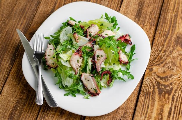 Salade de poulpe sur fond en bois.