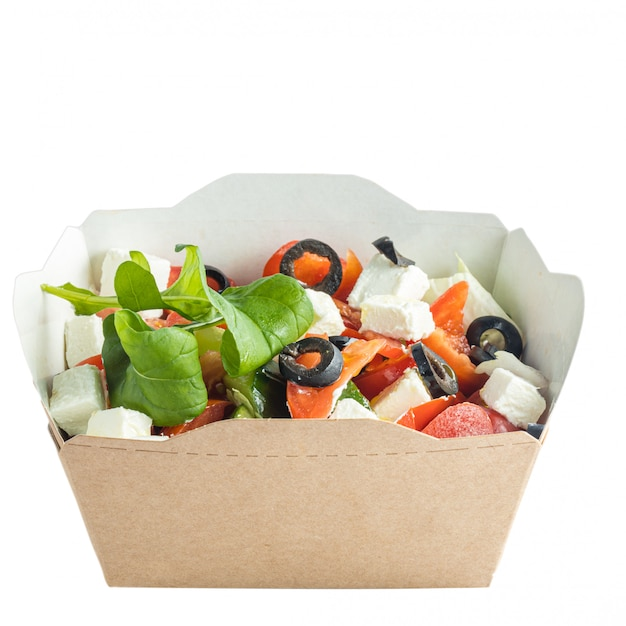 Salade pour aller dans une boîte en papier, isolé sur blanc