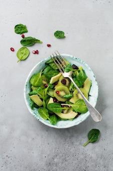 Salade de pousses d'épinards, cresson, kiwi, avocat et grenade dans une vieille assiette en céramique sur une surface de béton gris. mise au point sélective. vue de dessus. copier l'espace