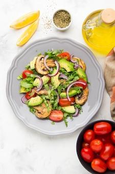 Salade printanière aux champignons, tomates cerises, avocat et oignons