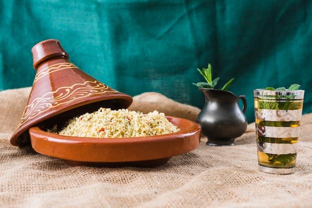 Salade de quinoa près de tasse et pichet sur toile de jute