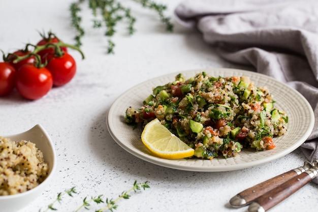 Salade de quinoa avec tomates fraîches, concombres et feuilles de salade. super aliment et saine alimentation.