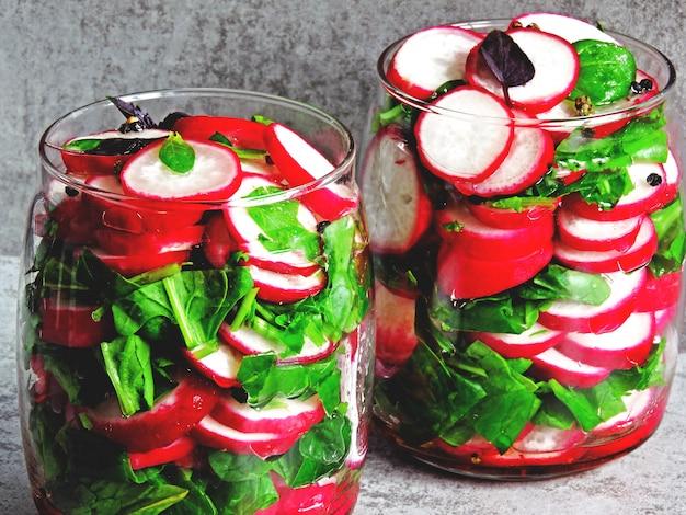 Salade de radis aux épinards dans un bocal. salade de fitness de légumes frais dans un pot. fermentation des légumes.