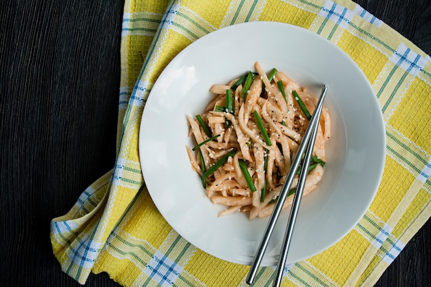 Salade de radis daikon, oignons verts, miel et poudre de chili rouge. salade asiatique. lay plat. . sombre .