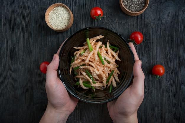 Salade de radis daikon, oignons verts, miel et poudre de piment rouge. salade asiatique. mise à plat. espace pour le texte. fond sombre.