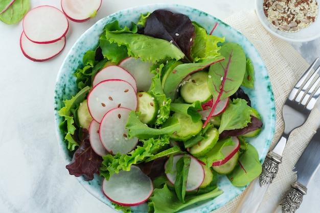 Salade de radis frais, roquette, betteraves, blettes, graines de tournesol, lin et graines de sésame sur une surface légère
