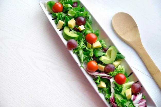 Salade de raisin à la tomate et à l'avocat avec une cuillère en bois