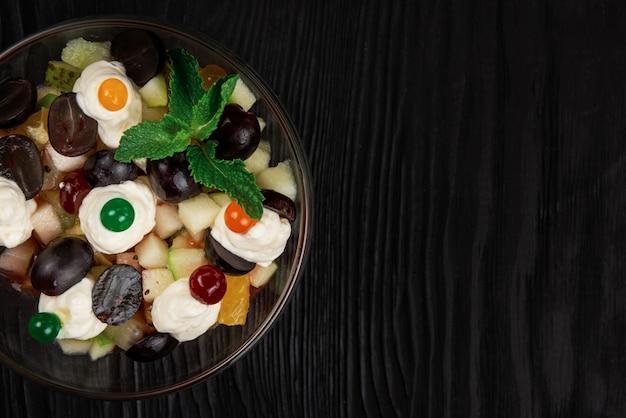 Salade de raisins pommes poires kiwis oranges avec fromage mascarpone et crème. salade d'été de fruits frais sains dans un bol en verre sur fond de bois noir avec espace de copie.