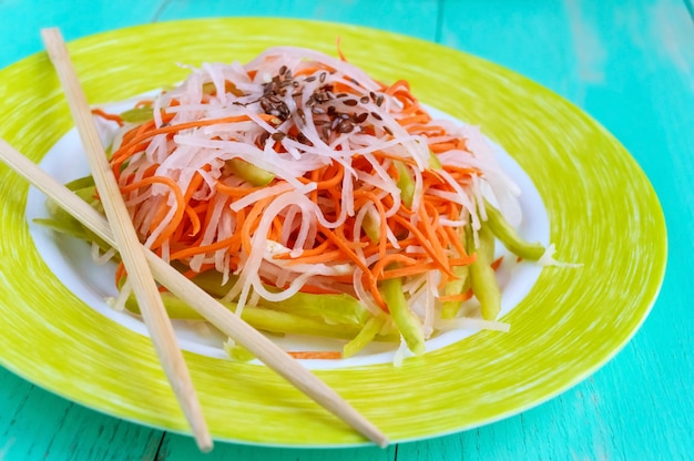 Salade de remise en forme diététique fraîche de radis daikon, carottes, graines de lin, roquette. cuisine végétalienne. fermer