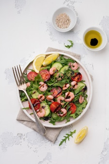 Salade de roquette, concombre, tomates et crevettes à la sauce soja sur une assiette en céramique