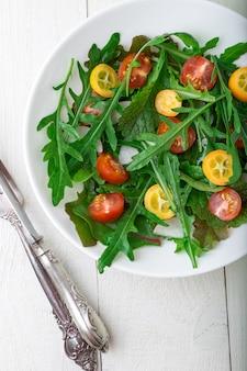 Salade de roquette fraîche avec kumquat et cerise tomate sur une surface en bois blanche,