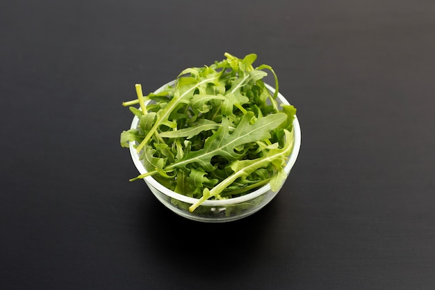 Salade de roquette verte fraîche dans un bol en verre sur une surface sombre.