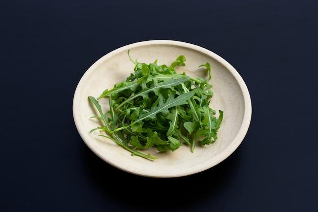 Salade de roquette verte fraîche sur une surface sombre.