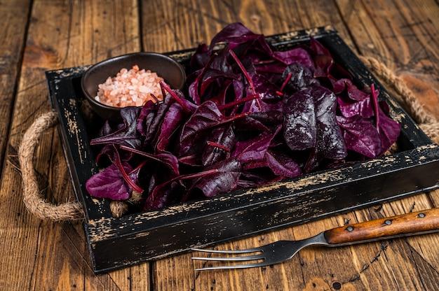 Salade de rubis suisse cru frais ou de bettes rouges feuilles dans un plateau en bois