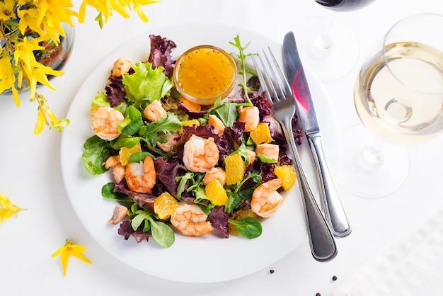 Salade saine aux crevettes servie dans une assiette avec un bol de sauce à la moutarde et à l'orange
