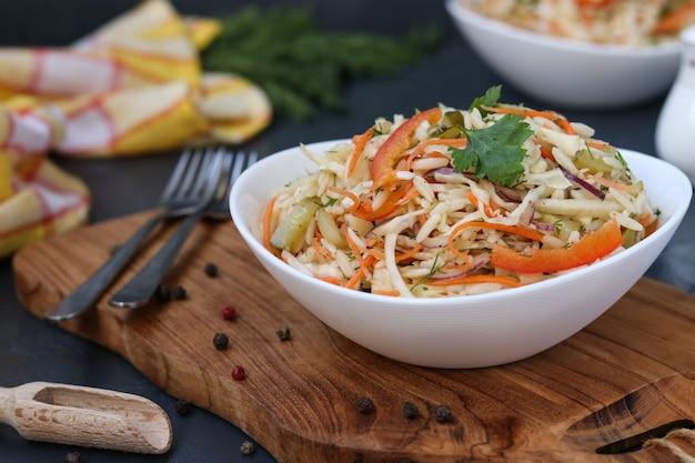 Salade saine de chou, poivron, oignon et pâtes orzo est situé dans un bol blanc sur une planche de bois, gros plan