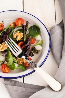 Salade saine dans un assortiment d'assiettes blanches