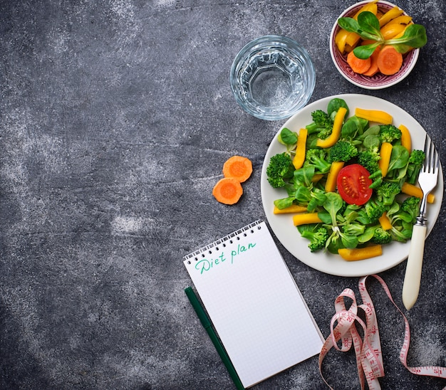 Salade saine, eau propre et ruban à mesurer.