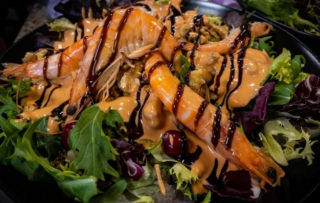Salade saine et fraîche aux crevettes et légumes servis dans l'assiette sur une table dans un restaurant au décor. belles langoustines apéritives à la rukola.