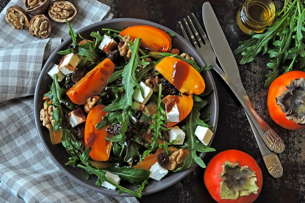Salade saine avec kaki, roquette, noix et fromage feta. nourriture de fitness. superfoods vitamine automne kaki salade.