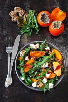 Salade saine avec kaki, roquette, noix et fromage feta.