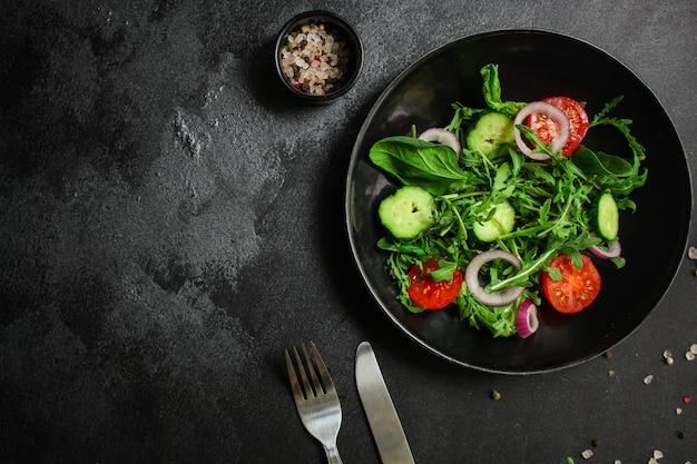 Salade saine, mélange de feuilles salade (mélange de micro-légumes verts, concombre, tomate, oignon, autres ingrédients)