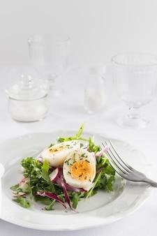 Salade saine avec des œufs sur un assortiment de plaques blanches