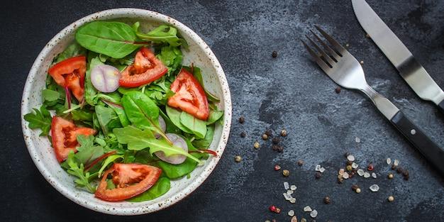 Salade saine de tomates, mélange de feuilles, oignons et autres ingrédients