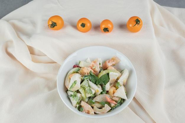 Salade de saison d'ingrédients mixtes avec légumes et fruits dans un plat blanc.