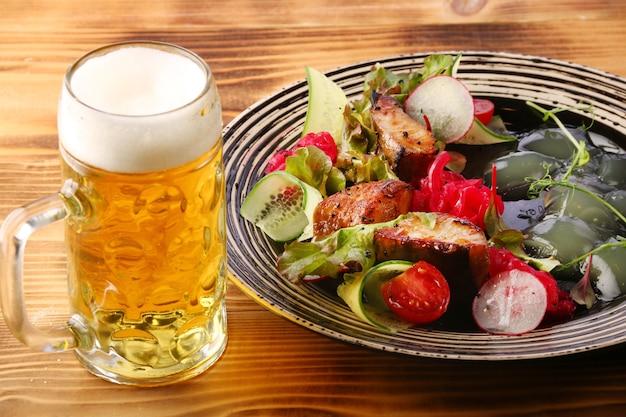 Salade de sandre aux légumes en assiette sur table en bois citron pour déjeuner de poisson et de bière