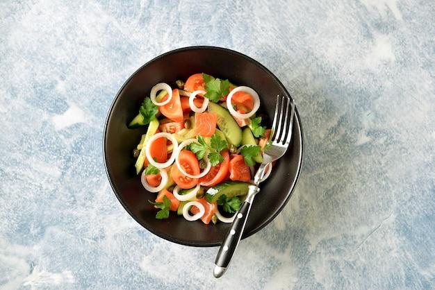 Salade santé de tomates cerises, concombre, céleri, oignons, câpres et persil au saumon salé.