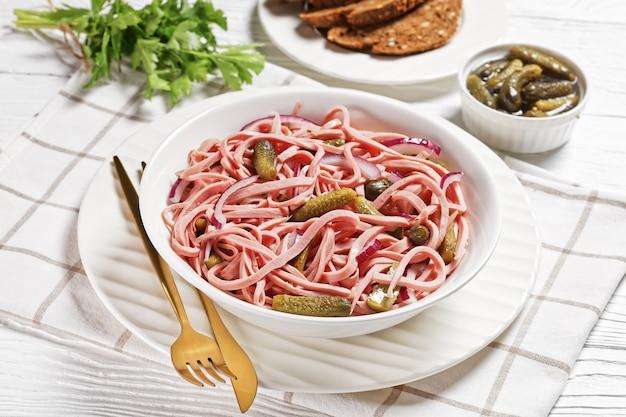 Salade de saucisse allemande de saucisse de lyoner tranchée avec cornichons et oignon rouge servie sur une assiette blanche avec des couverts dorés et du pain de seigle sur un fond en bois blanc, vue de dessus, gros plan
