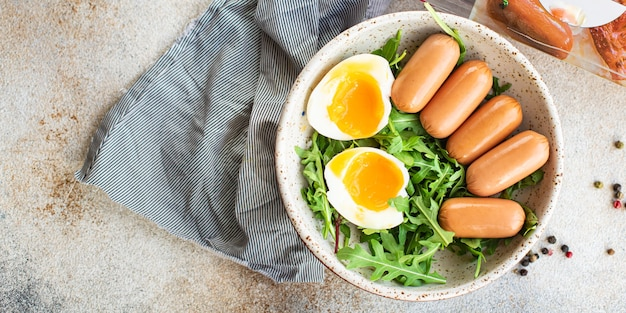 Salade de saucisses oeuf poché feuilles pétales verts mélange de laitue frais en bonne santé