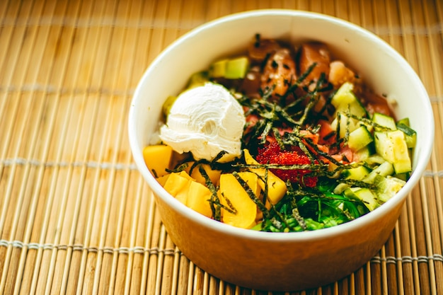 Salade de saumon asiatique avec mangue, fromage à la crème et légumes pour une alimentation saine, service de livraison de nourriture et concept de commande en ligne