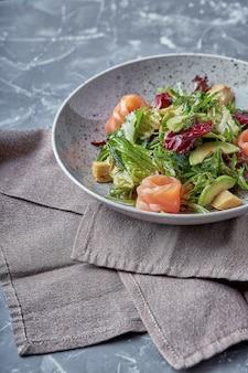 Salade de saumon aux épinards, salade de maïs, petits épinards, menthe fraîche et basilic. nourriture faite maison. concept pour un repas savoureux et sain. fond de pierre sombre. vue de dessus. fermer.