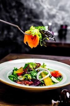 Salade de saumon câpres aux œufs d'orange tomate séchée au soleil basilic vue latérale