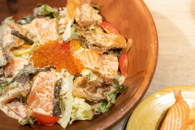 Salade de saumon composée de divers légumes, saumon frais, peau de saumon et œufs servis dans un bol en bois