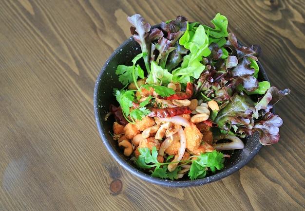 Salade de saumon épicée frite de légumes et d'herbes.