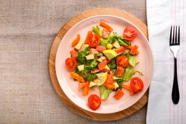 Salade de saumon et tomates cerises et salade verte dans une assiette sur une table en bois sur un support en bois avec une fourchette et une serviette à côté.