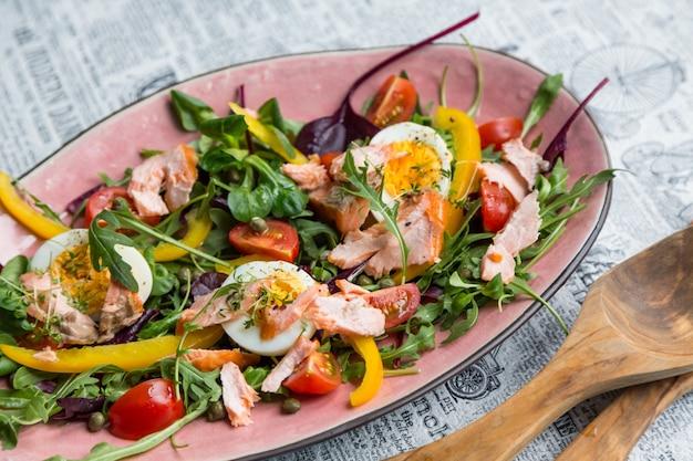 Salade de saumon et verdure en plaque rose sur fond de journal rétro