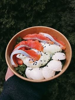 Salade savoureuse saine avec œuf de saumon poché à la roquette dans une boîte en carton dans une main sur fond de bois vert. livraison de nourriture. photo de haute qualité