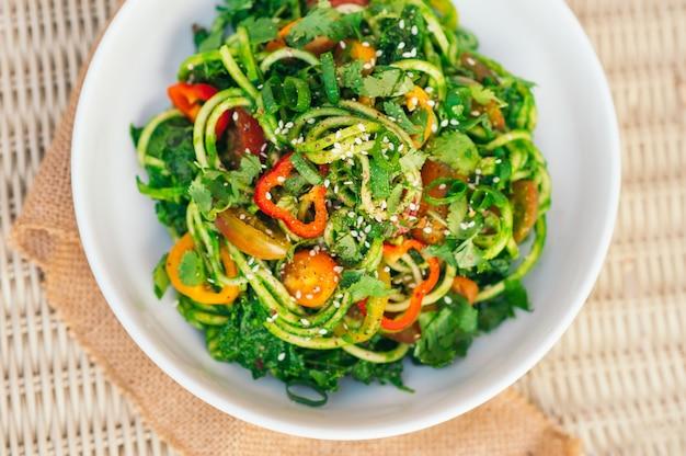 Salade de spaghetti aux courgettes avec tomates jaunes, poivron rouge, oignon, graines de seasame, coriandre dans un bol blanc. salade fraîche sur la table. plat de légumes. vue de dessus horizontale
