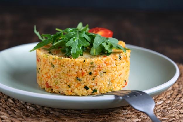 Salade taboulé couscous végétarien aux légumes, décorée de roquette