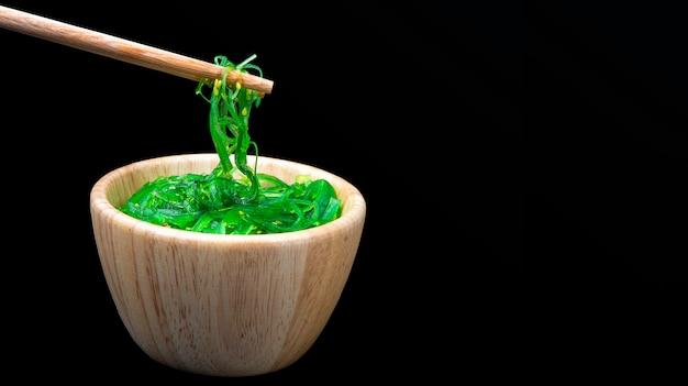 Salade takaki en cubes avec salade d'algues, saupoudrée de graines de sésame dans une tasse en bois