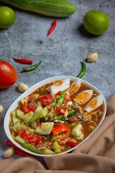 Salade thaïlandaise épicée avec concombres et poivrons dans des œufs salés.