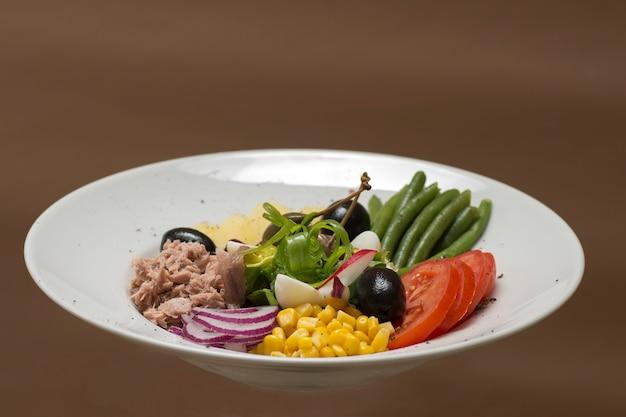 Salade de thon aux légumes, posée sur une assiette blanche, fond marron