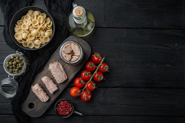 Salade de thon aux pâtes et légumes ingrédients sur table en bois noir, mise à plat