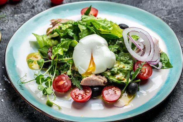 Salade de thon aux tomates, olives noires, oeuf poché, laitue, cerise, tomates olives
